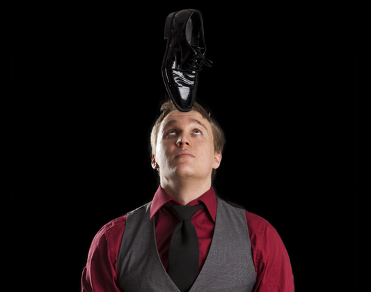 Lauri doing stand-up magic and balancing shoe on his head